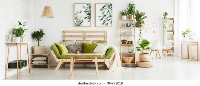 Wooden table in front of green couch with cushions in floral living room interior with leaves posters and suitcase on shelf