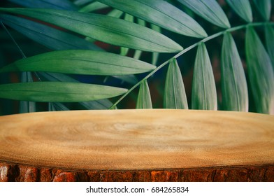 wooden table in front of tropical green floral background. for product display and presentation.