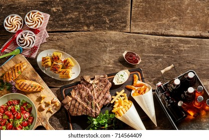 Wooden table full of grilled meat with french fries, beer, ice cream and salad