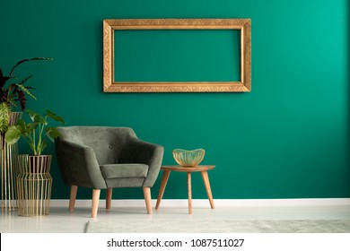 Wooden table with gold, metal bowl standing by a green armchair in living room interior with frame on the wall