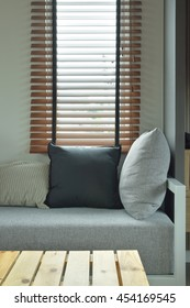 Wooden table with gray color cushion and pillows next to window
