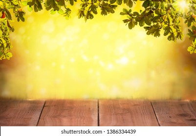 Wooden table with green leaves and blurred spring background