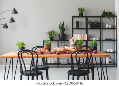 Wooden table with healthy food in grey dining room interior with black chairs and plants. Real photo