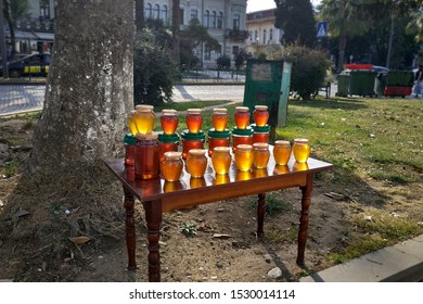 A wooden table with jars of amber honey stands at the side of the road. Near the tree by the road there is a table with honey. Honey is sold in jars in Georgia.