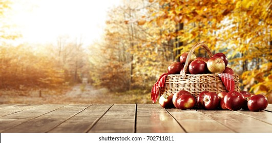 Wooden table in the kitchen with fresh apples in a wicker basket