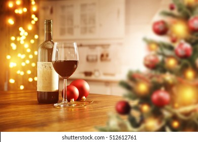 Wooden table in kitchen place and christmas wine on top with blurred xmas tree