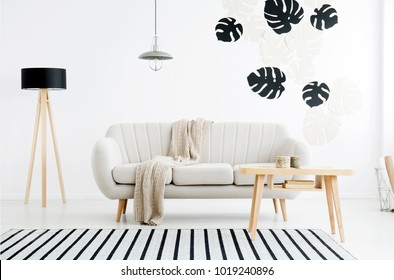 Wooden table and lamp near beige sofa against white wall with leaves stickers in living room interior
