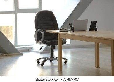 Wooden table with laptop and chair in office