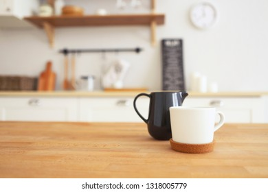 Wooden table with mug and milk jug with blurred kitchen background, copy space