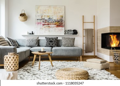 Wooden table next to grey corner settee in warm living room interior with painting and fireplace. Real photo
