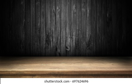 Wooden table on black wall in dark room background.