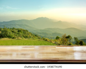 Wooden table on blur mountain morning or evening view landscape, Warm feeling in orange or brown tones.