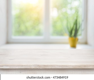 Wooden table on blurred autumn window with plant pot background