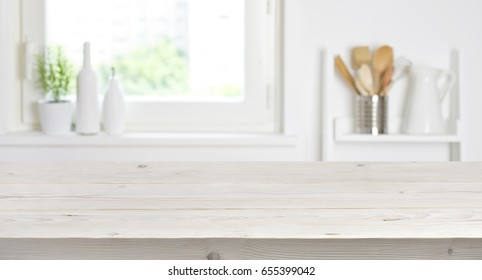 Wooden table on blurred background of kitchen window and shelves - Shutterstock ID 655399042