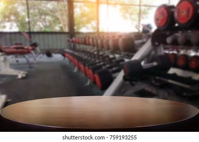 Wooden table on blurred background of fitness gym interior of modern club with equipment for your photomontage or product display