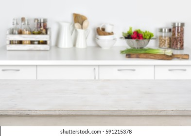 Wooden table on blurred kitchen interior background with fresh vegetables.