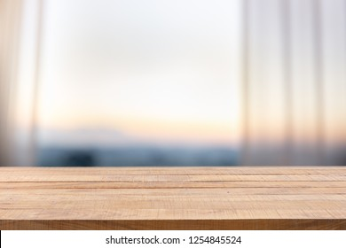 Wooden table on defocused curtain window and stationery box with Defocused curtain window with sunlight in the early morning.