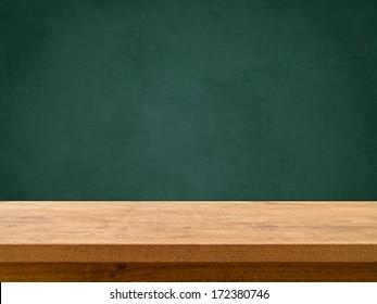 Wooden table on green chalkboard