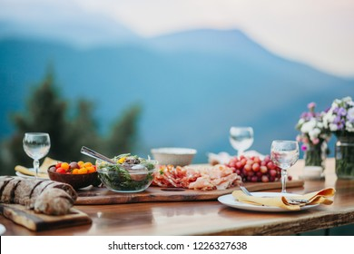 Wooden Table on Mountain Top with Salad and Salami Platter