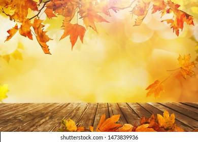 ein Holztisch mit orangefarbenen Herbstblättern, natürlicher Hintergrund