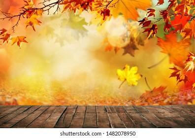 hölzerner Tisch mit orangefarbenen Herbstblättern, natürlicher Hintergrund