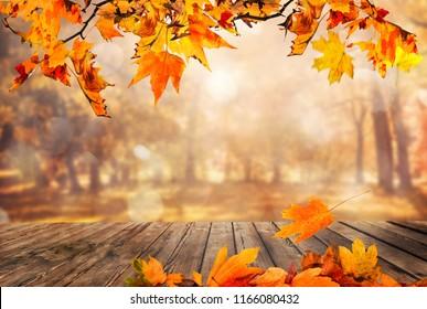 hölzerner Tisch mit orangefarbenen Blättern Herbsthintergrund