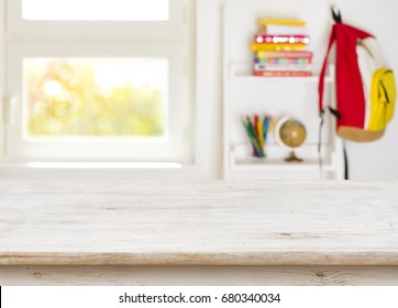 Wooden table over blurred background of junior schoolchild room interior