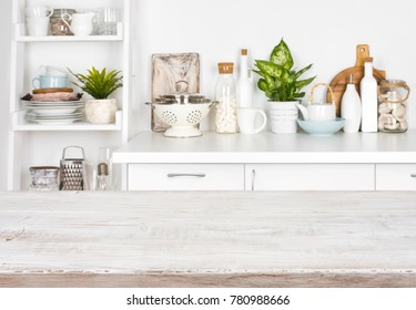 Wooden table over blurred image of kitchen bench and shelf