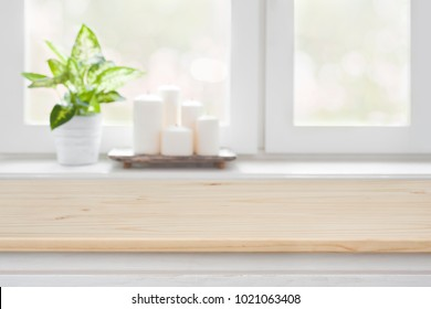 Wooden table over blurred window sill background for product display