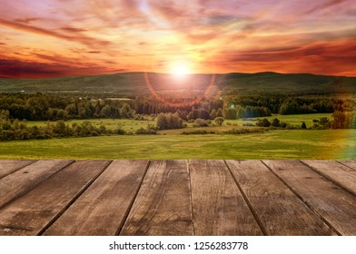 Wooden table perspective and a mountain landscape in background. Sunny summer day.