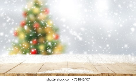 Wooden table place. Space for your decoration. Snow on top of board. Christmas tree on background.