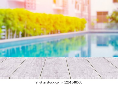 Wooden table with pool summer background.