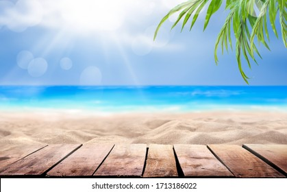 A wooden table product display with a summer vacation, holiday background of a tropical beach, blue sea, white clouds, sun flare and green palm tree leaves.