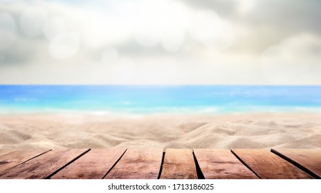 A wooden table product display with a summer vacation, holiday background of a tropical beach and blue sea and white fluffy clouds and sun flare.