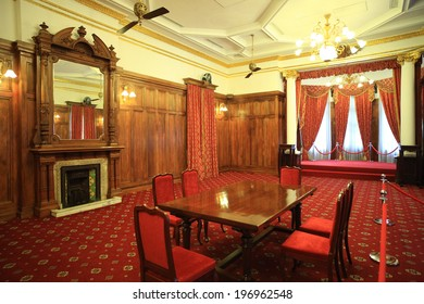 A wooden table with red chairs in the middle of a room.
