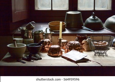 Wooden table with rustic kitchen utensils near the window in old kitchen