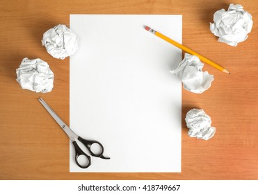 wooden table with scissors,sheet of paper and pencil