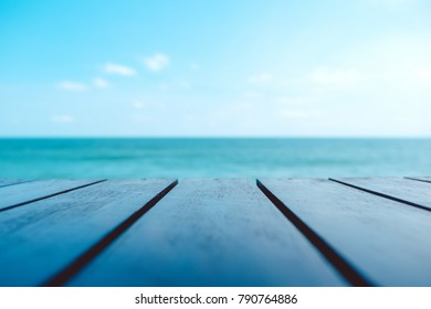Wooden table with the sea and blue sky background