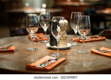 wooden table served with plates, forks, spoons, glasses, napkins in the restaurant