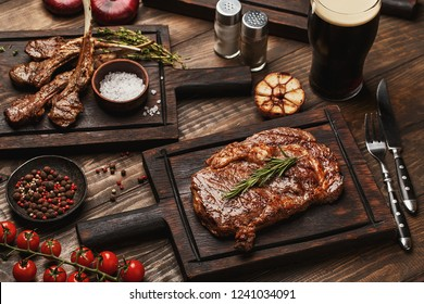 Wooden table served with various grilled meat, vegetables and glass of beer. Ribeye steak and lamb ribs on wooden cutting boards