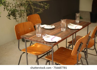 A wooden table set, with three plat on the fork and knife, spoon, and glass cups, wooden chairs without some food