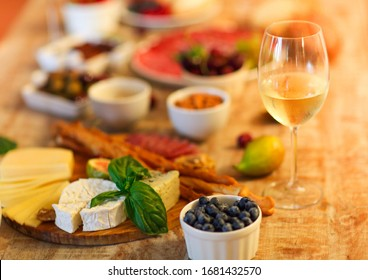 Wooden table set with white wine and assorted delicious snack of cheese and olives in living room in the evening