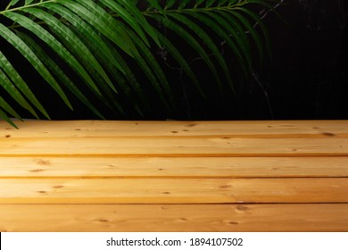wooden table for show product display and presentation, palm leaves and dark marble background, copy space, selective focus.