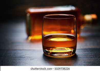 Wooden table with single shots of whiskey and full bottle