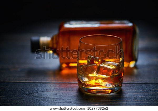Wooden table with single shots of whiskey with ice . full bottle