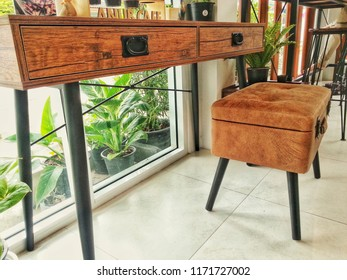 Wooden table with soft chair in the glass room.