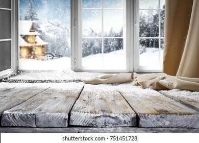 Wooden table with space for your product. Curtain in the window. Open window with snowflakes. Landscape of winter forest. Morning sunshine.