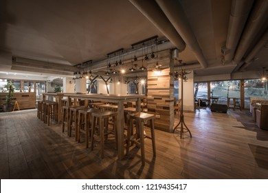 Wooden table with stools in restaurant interior
