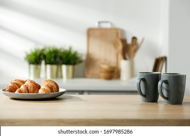 Wooden table in a sunny kitchen in the morning light during breakfast