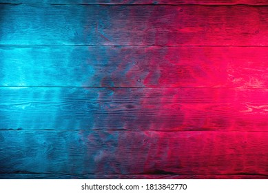Wooden table surface in neon lights abstract background.